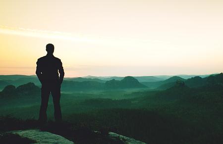 Zaino in spalla alto a bordo Escursionista con zaino in piedi sul punto panoramico roccioso sopra la valle. Effetto vignettatura vivido e forte. Archivio Fotografico