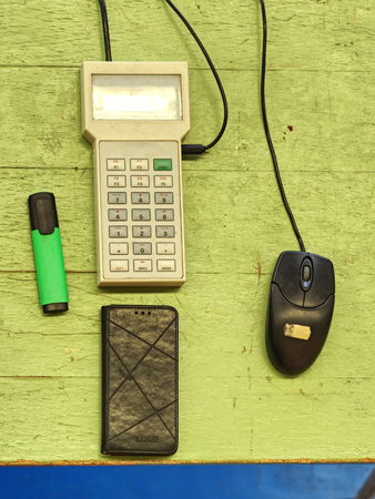 Data keyboard terminal on wooden board. Green highlighter and black cable. Key board of small remote control