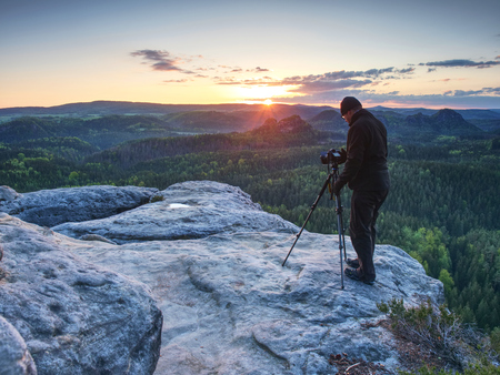 Tall adult photographer prepare camera for taking picture of fall mountains. Photograph at daybreak above colorful valley.