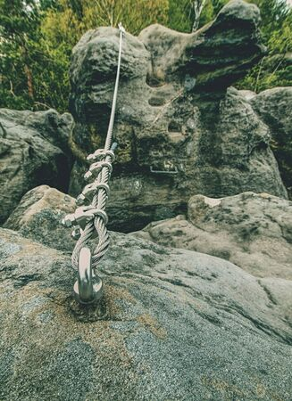 Climbing carabiner on a steel rope between rocky peaks on via ferrata