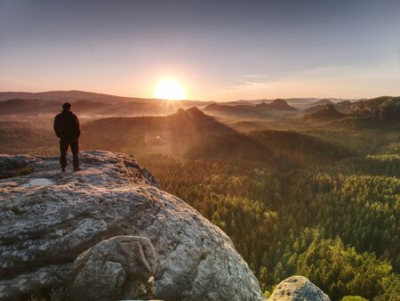 Man on the rock empire with hands in trousers pocket  watch over the misty morning valley to rising sun at horizon.