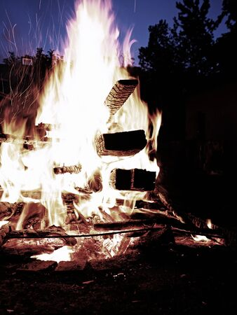 Cleaning old wooden stuff by fire. Close up of big flames fire with red and yellow flames in the night