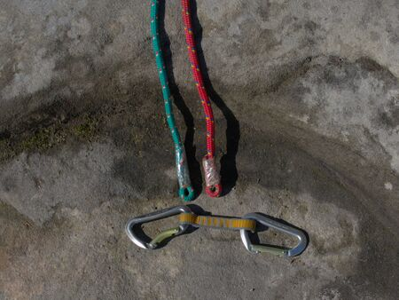 Climbing equipment - detail carabiners and rope. Ascender placed on rock at old rope. Hank sling carabiners