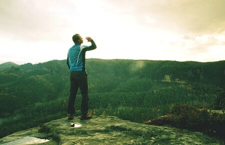 Man on a cliff edge on the top of mountain with gorgeous view and drink water