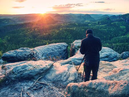 Photographer with tripod on cliff and thinking. Dreamy foggy landscape orange misty sunrise in a beautiful valley below