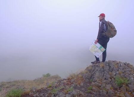 Seitenansicht des Wanderers mit Rucksack-Lesekarte, die im Nebel wegschaut