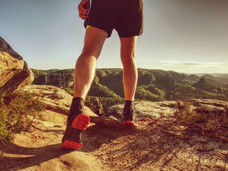 Trail runner run in natural terrain, body contour in low ankle view, detail if body.