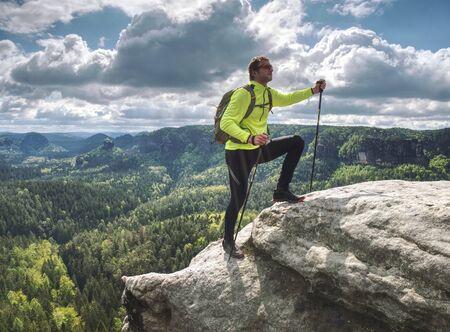 uomo zaino in spalla che corre sul bordo della scogliera in cima alla montagna. Avventura del concetto di stile di vita di viaggio e sentiero, vacanze estive all'aperto Archivio Fotografico