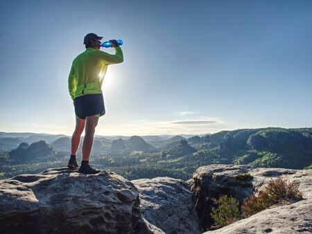 Fit runner in sport suit drinking the water from sport bottle with relax action in deep forest in morning time Stock Photo - 126876558