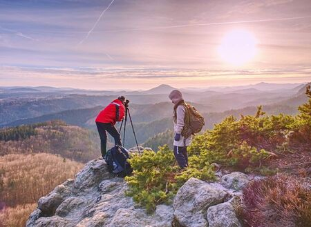 Hiker and photographer stay with tripod on cliff and takes photos. Two people stay at tripod on background of mountain range and sky with clouds