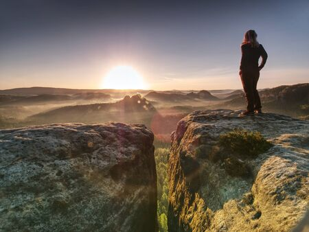 Alone woman hiker model in wild nature within marvelous sunrise. Misty valley somewhere in hilly ladscape. Imagens
