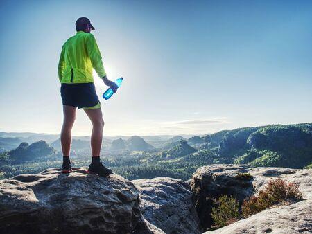 Deportes botella beber deporte hombre agua potable en trail run. Corredor masculino sudoroso y sediento después de un entrenamiento difícil.