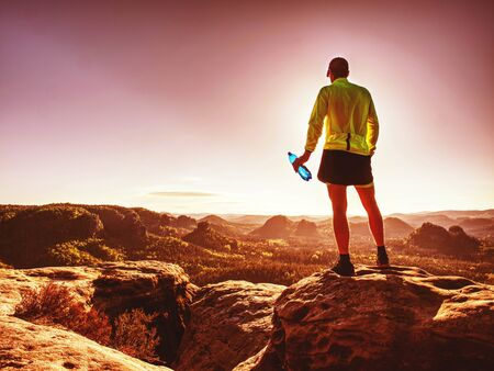 Fit runner in sport suit drinking the water from sport bottle with relax action in deep forest in morning time