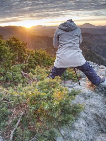 Woman photographer works. Professional artist takes photos with mirror camera and tripod on peak of rock. Dreamy fogy landscape spring orange pink misty sunrise in beautiful valley below.