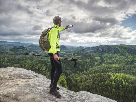 Backpacker with phone in hand. Sunny spring valley in rocky mountains. Hiker with backpack stand on rocky view point