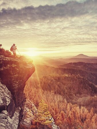 Nature photographer takes photos on danger rocky edge. Artist woman with mirror camera on peak of rock. Dreamy foggy landscape spring orange pink misty sunrise Banque d'images