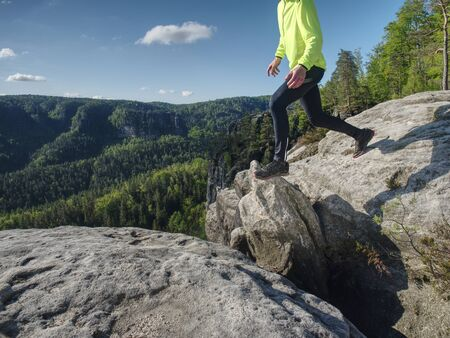 Man athlete while jumping during a trail running in the mountains. Sportsman Legs Running on the Rocky Mountain Trail.
