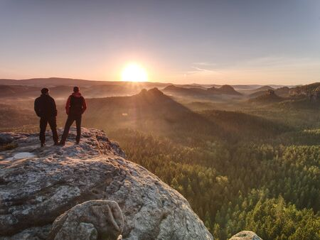 Two guys stay close to edge on cliff, watching awakening nature below summit. First warm sun beams of sunrise.