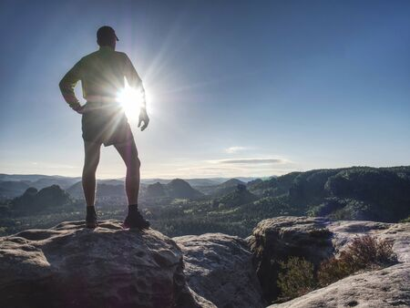 Trail runner athlete man. Slim person training in mountains in cold weather at sunset. Amazing mountain peaks in the background. Stock Photo - 127435628
