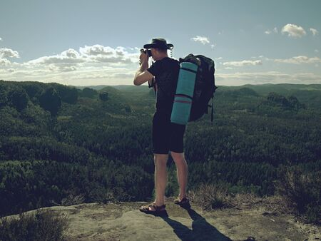 Traveler with a backpack admires a tranquil natural landscape. Concept active recreation in mountains.