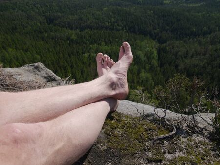 Tired hikers legs without shoes. Man hiker legs climbed at mountain peak rock