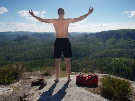 Middle age shirtless man just in black shorts with backpack and leather sandals resting on rocky edge with fantastic view into wild nature.