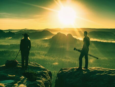 Couple tourist with photo camera at top of mountain watch sunset outdoors during a hike in pure nature