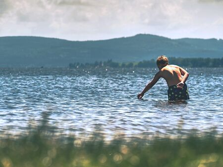 Kid stay in cold spring lake in cold weather. Muscular body of boy.