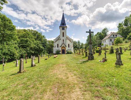 Church and graveyard in Zadni Zvonkova,  a border village ruined by the communist regime.  15th of July 2019, Zadni Zvonkova, Czech Republic. 스톡 콘텐츠