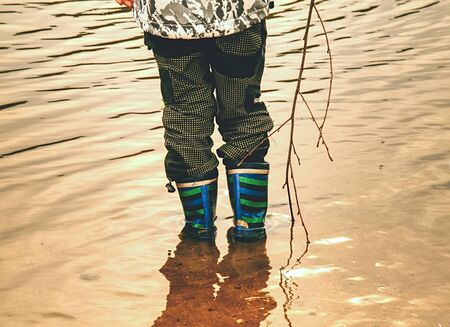 Young children with boot walk in dirty muddy water. The flood after rain in village