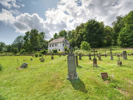 Church of st. John of Nepomuk and Graveyard, Zadni Zvonkova, Czech Republic. 15th of July 2019.  Neo-Gothic building in an abandoned border village with a troubled history. 스톡 콘텐츠