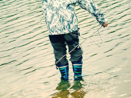Boy legs rubber boots standing in muddy dirty pool in countryside, feet from above