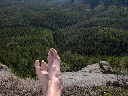 View over own legs to the word. rest on sandstone rock above valley. Long forest valley in hilly landscae of nature park.