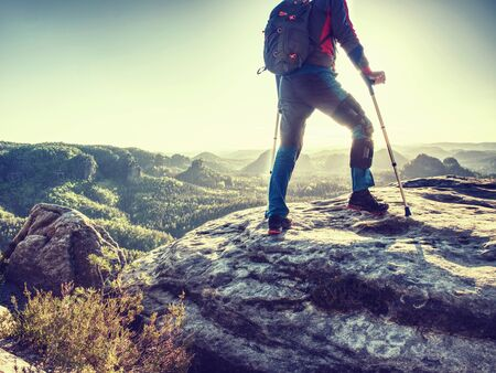 Happy man hiker hold medicine stick,  injured knee fixed in knee brace feature. Scenic mountain top with deep misty valley bellow Imagens