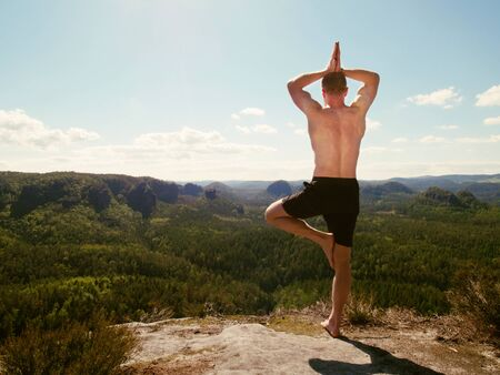 Shirtless tall caucasian man wear black shorts rests on top of mountain peak after a successful climb