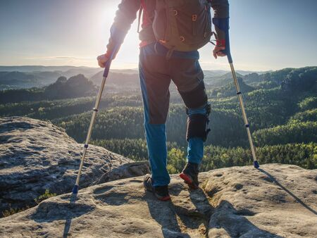Hiker man with broken leg in immobilizer and forearm crutches. Deep misty valley bellow silhouette of man with hand in air. Spring daybreak Stock Photo