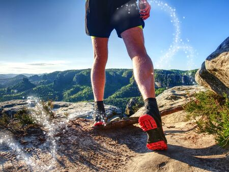 Sportsman on trail. Slim body man in yellow jersey, black shorts and running shoes run in wild nature. Abstract filter. Stock Photo