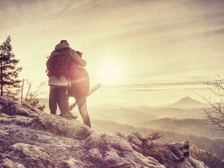 Silhouette man and girlfriend shooting sunset on the top mountain. Photographer with eye at viewfinder of camera on tripod stay on cliff and takes photos talk woman friend