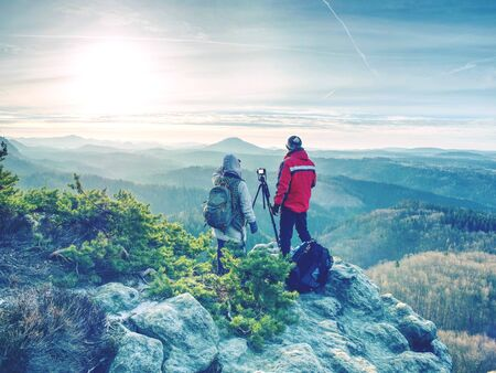 Couple of hikers look down into fogy valley. Photographer stay on cliff and takes photos. Dreamy fogy landscape blue misty sunrise in a beautiful valley below 版權商用圖片