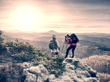 Man photographer and woman traveler photographing with camera on the tripod. Two people taking a shot of the mist covered mountains and the rocks