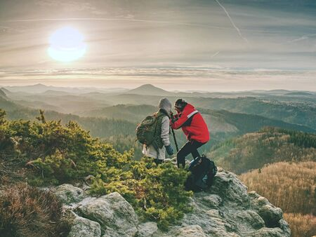 Hiker and photographer stay with tripod on cliff and takes photos. Two people stay at tripod on background of mountain range and sky with clouds 版權商用圖片