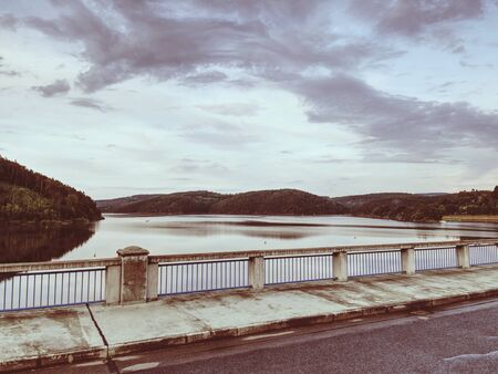 View over foot bridge handrail to dam water level. Evening cloudy sky.