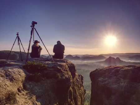Couple of extreme creative artists work and talk on exposed rock ledge with beautiful view into wild nature. Woman and man takes impressive photos together. Banco de Imagens