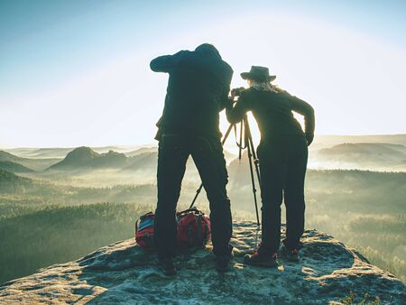 Photographer check viewfinder of camera on tripod and framing natural scene. Lady and man create art on cliff and takes photos Stockfoto