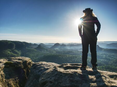 Adult cow woman standing on a rock with head held. Beautiful Sunrise view and sea of mist in morning Stock Photo - 130069197