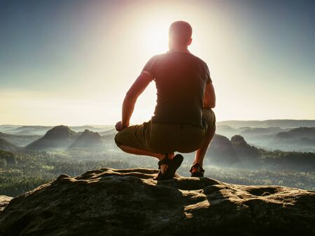 Sports man in outoor clothes and boots walking on rocky peak. Summit of mountain and look on the nice fog view. Concept freedom