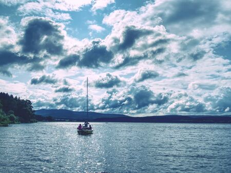 Small sailing boat anchoring next to a buoy in the calm water of lake, moody tones Stok Fotoğraf - 130069276