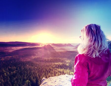 Tall girl tourist enjoy successful achievement of summit with fantastic view into morning hilly landscape. Abstract filter.