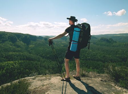 Traveler with backpack and trekking sticks looks on a mountain peak. Hiker with sleeping pad. 스톡 콘텐츠