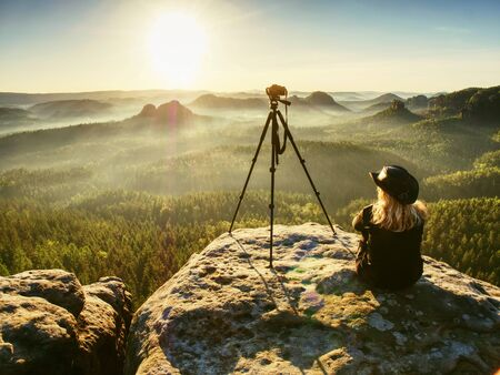 Tourist girl and photographer looking at the misty fog mountains from rocky viewpoint. Traveling outdoor hiking walking nature.